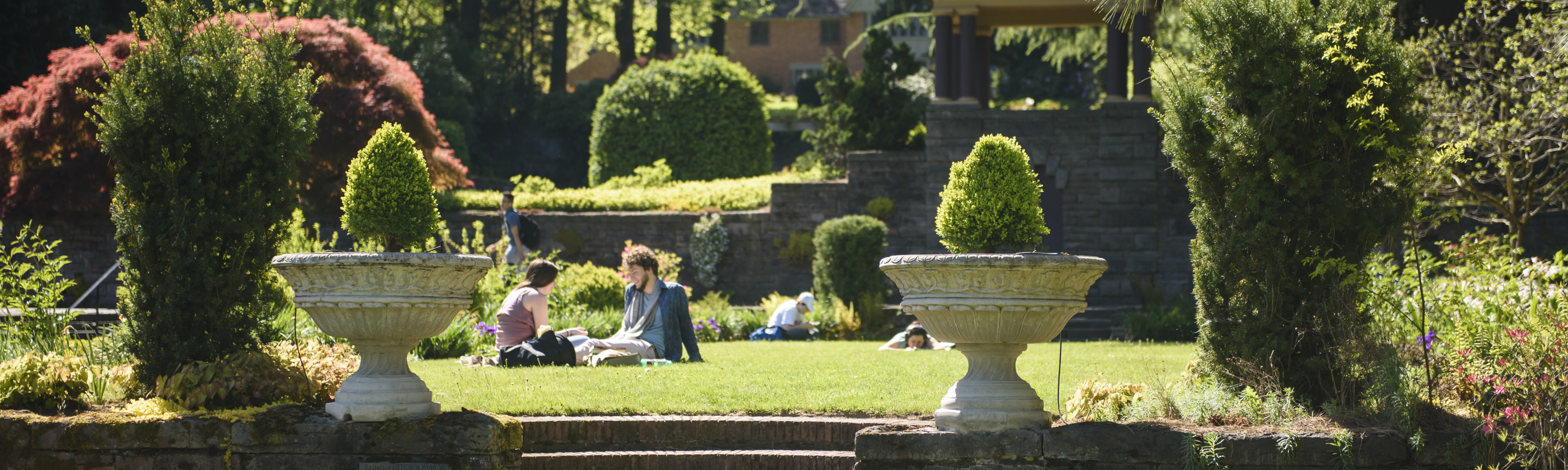 Students sitting on the grass in the Estate Gardens.