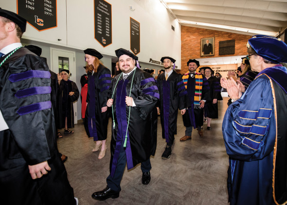 Procession of graduates amidst faculty applause.