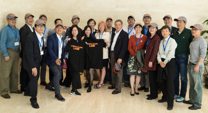 The alumni reunion group pose with Lewis &  Clark Law School swag.