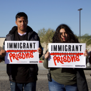 "Three people hold up signs reading, ""Immigrant Prisons"""