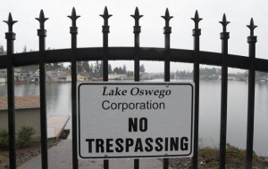 A sign indicates restricted access to Oswego Lake in Lake Oswego.